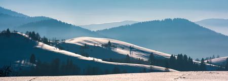 雪の降る丘陵のゴージャスな冬のパノラマ。遠くに森の山々がある美しい風景