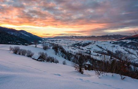 winter dawn in mountainous countryside. gorgeous cloudy sky over the snow covered hills. wide mountain ridge in a far distance Banco de Imagens