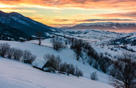 山間の田園地帯で冬の夜明け。雪に覆われた丘の上の豪華な曇り空。遠い距離の広い稜線