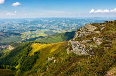 山の丘の端にある岩場の崖。晴れた夏の日に渓谷へのゴージャスな景色