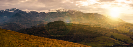 great mountain ridge Borzhava with snowy tops at sunset. beautiful countryside landscape in late autumn Stock Photo