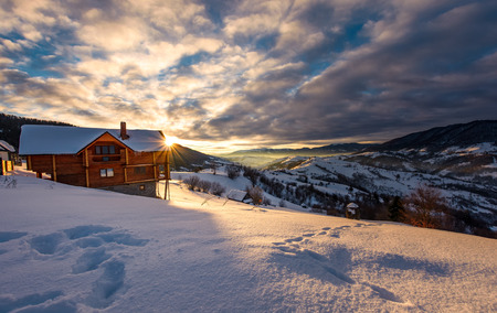 wooden chalet in village outskirts at sunrise. gorgeous landscape in winter Carpathian mountains, great place for vacation
