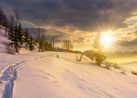 rural footpath through snowy hillside at sunset. beautiful scenery of mountainous countryside in winter