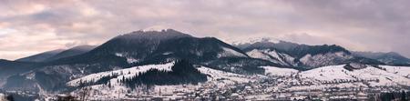 日の出山の尾根のパノラマ。曇り空の下で雪のピークを高いと豪華な冬の風景