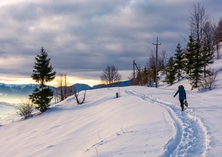 人は、雪に覆われた丘の中腹を通過します。冬の山間の田園地帯の美しい風景 写真素材