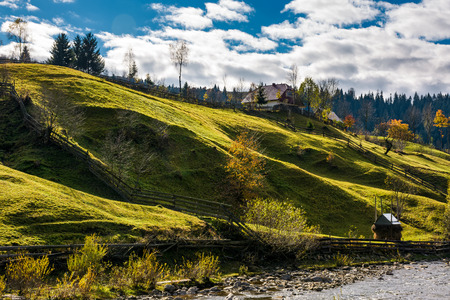 grassy rural hillside near the village in autumn. beautiful countryside scenery Stock Photo