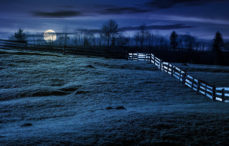wooden fence on grassy hillside in autumn. wonderful rural scenery in fine weather with cloudy sky at night in full moon light