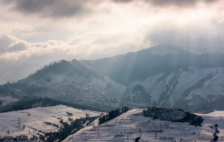 sunbeams through clouds over the snowy mountains. beautiful countryside scenery in winter Stock Photo