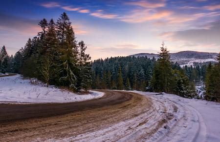 겨울 산에서 뱀 위에 화려한 황혼. 스프루스 숲의 도로 전환