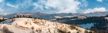 冬カルパチア山地の農村地帯のパノラマ。農業分野や雪の斜面のトウヒ林。遠くに巨大な山の尾根 写真素材