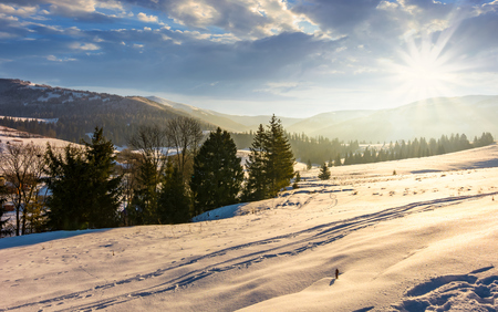winter time in mountainous rural area. gorgeous countryside with forested hills and snowy meadows at the foot of mighty mountain ridge Stock Photo - 90420505