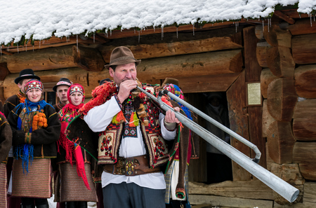 Uzhgorod, Ukraine - January 15, 2017: Carols in old village festival in TransCarpathian Regional Museum of Folk Architecture and Life. Man in national suit plays iron trembita Editorial