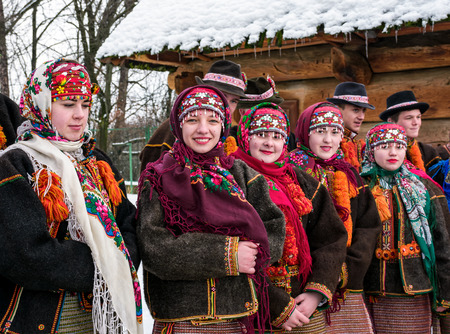 Uzhgorod, Ukraine - January 15, 2017: Carols in old village festival in TransCarpathian Regional Museum of Folk Architecture and Life. Girls in national suits singing carols outdoors give a smile Editorial