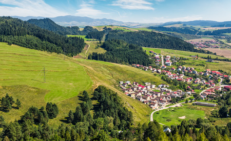 Slovakian town Stara Lubovna on grassy hillside. beautiful rural scenery in mountainous area viewed from above on a summer day.  Stock Photo