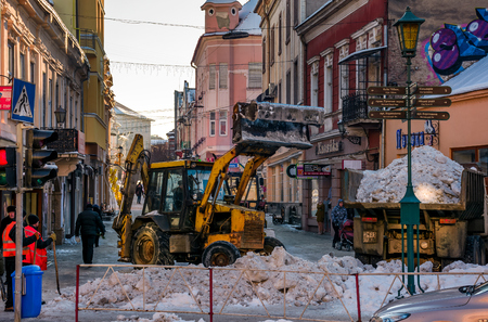 Uzhgorod, Ukraine - January 19, 2017: snow removal on streets of old town. people remove snow huge amount of snow with the help of shovels and tractor Stock Photo - 90644806