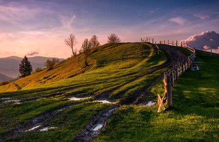 wooden fence along the country dirt road uphill the grassy knoll in springtime at dusk. Spectacular nature scenery in mountainous rural area with gorgeous pink sky with some clouds Stock Photo