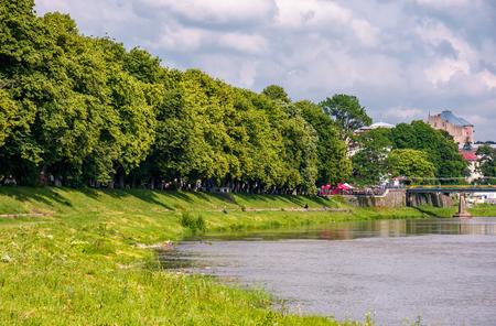 part of a longest linden alley in Europe. Uzh river embankment of Ukrainian town Uzhgorod in summer Stok Fotoğraf - 90944049