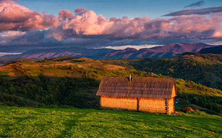shed on the grassy hillside in red evening light. gorgeous springtime rural landscape in mountains under the blue sky with pink clouds Stock Photo