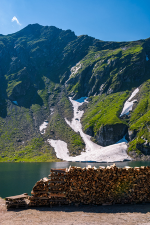 chopped firewood on the shore of a glacier. beautiful summer scenery in mountains. rocky hill with some grass and spots of snow.