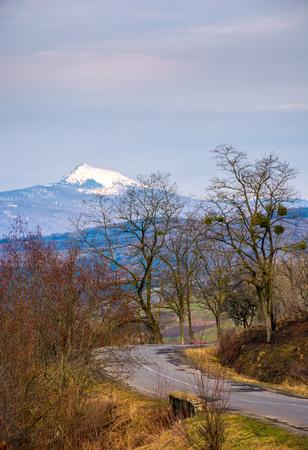 春の森林の丘を通るアスファルト道路のターンアラウンド。遠くに山の尾根の高い雪のピークが見られる 写真素材