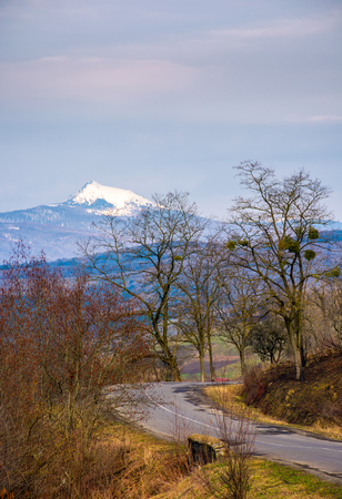 asphalt road turnaround through forested hills in springtime. high snowy peak of mountain ridge is seen in the distance