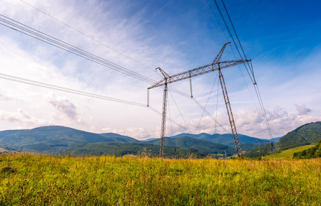 high voltage power lines tower in Carpathian mountains. lovely green energy industry concept. beautiful landscape in autumn with blue sky and some clouds Stock Photo