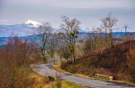 春の森林に覆われた丘をアスファルト道路転換。距離に山の尾根の高雪のピークが見られる