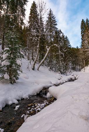 冬の森のカスケードを持つ小川。美しい冬の自然の風景