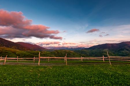 日没で草に覆われた丘の上の木製のフェンス。山の尾根に赤みがかった雲がかかる美しい田園風景 写真素材