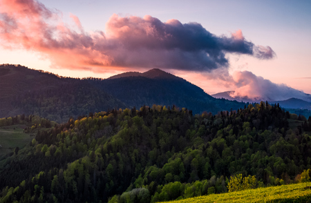 Pink cloud over the peak of a forested mountain. lovely springtime background of a mountainous countryside at sunset Stock Photo