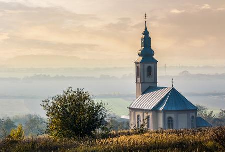 해질녘 헷갈리는 농촌 계곡 언덕에 교회. 사랑스러운 가을 전원 풍경 스톡 콘텐츠