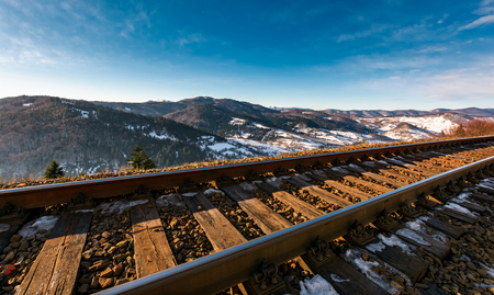 railroad in mountains with snowy slopes. lovely transportation scenery on winter sunny day Stock Photo