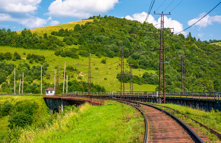railroad viaduct through forested hills in summer. lovely transportation scenery in Carpathian mountains, Skotarske, Ukraine Stock Photo