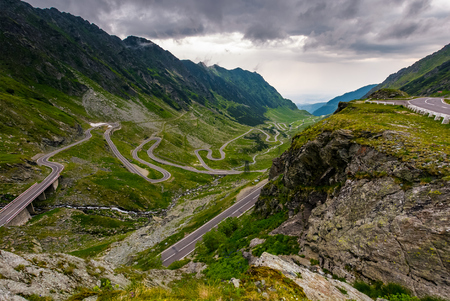 great Transfagarasan rout in stormy summer weather. great transport concept. gorgeous high altitude landscape on a rainy day. winding serpentine in Southern Carpathian Fagaras Mountains of Romania Stok Fotoğraf - 91941405