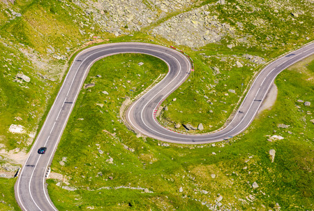 Transfagarasan road in Romanian mountains. winding serpentine among the grassy hills on a sunny morning Stock Photo