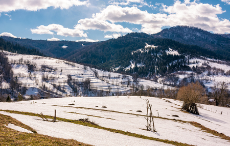 spring is comming. last days of winter landscape. rural field with weathered yellow grass covered with snow. village at the foot of the mountain ridge Stock Photo