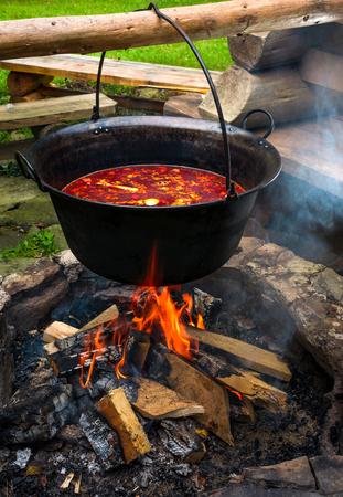 伝統的なハンガリーグーラッシュスープの大鍋。暖炉の上で屋外で調理された食事。中央ヨーロッパで人気の美味しく健康的な食べ物 写真素材