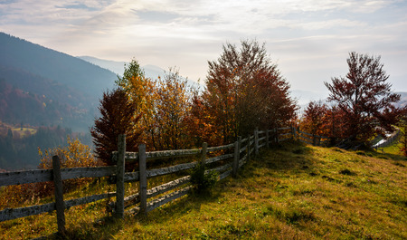 fence along the grassy hillside. beautiful autumn scenery in mountains. calm rural life concept Stock Photo