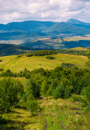beautiful countryside of Crapathians in early autumn. forested hills and mountain ridge with high peak in the distance. lovely sunny weather with cloudy sky Stock Photo