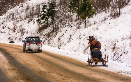 Volovets, Ukraine - December 16, 2016: traffic in mountainous rural area in winter. cart with one horse outscored by SUV on snowy countryside road Editorial