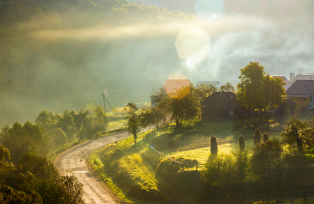 smoke and fog over the village at sunrise. beautiful rural scenery near the road in mountainous area Stock Photo