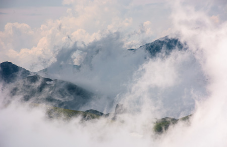 cloud formation in mountains on high altitude. spectacular natural phenomenon in summer. lovely weather background of hills with snow and grass