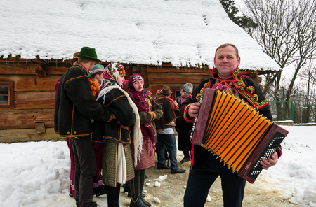 Uzhgorod, Ukraine - January 15, 2017: Carols in old village festival in TransCarpathian Regional Museum of Folk Architecture and Life. Man in national suit plays accordion