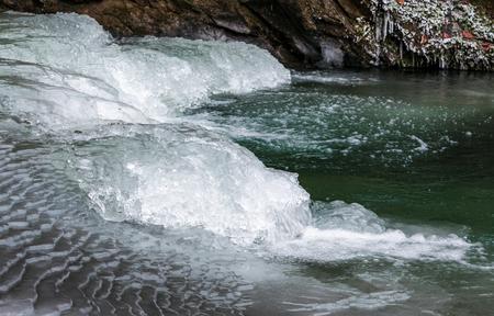緑がかった水で凍った川の上の氷。冬の美しい自然の背景 写真素材