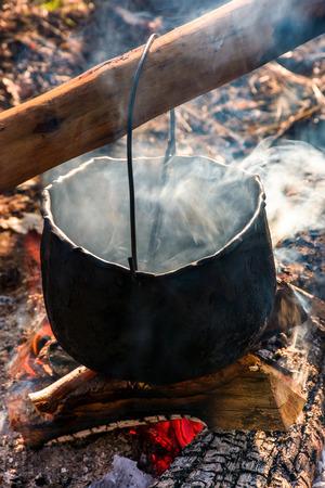 蒸気と煙で火の中の大釜。屋外料理のコンセプト。食べ物を作る昔ながらの方法