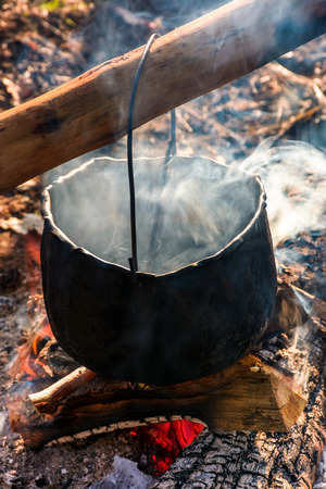 ketel in stoom en rook op open vuur. buiten koken concept. ouderwetse manier om voedsel te maken