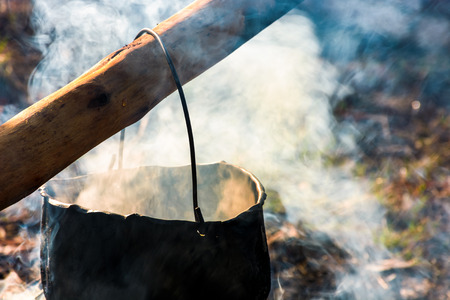 cauldron in steam and smoke on open fire. outdoor cooking concept. old fashioned way to make food 版權商用圖片