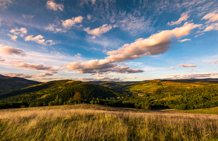 grassy slope in mountainous countryside at sunset. beautiful landscape with gorgeous cloudscape over the hills of Carpathian mountains. location Nyzhni Vorota, Volovets district of TransCarpathia, UA Stock Photo