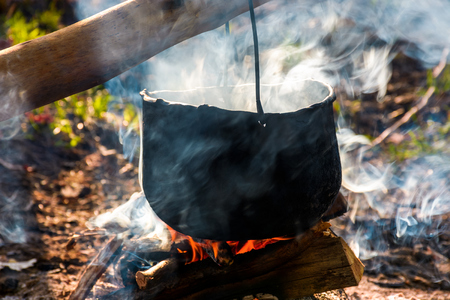 cauldron in steam and smoke on open fire. outdoor cooking concept. old fashioned way to make food Stock Photo