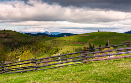 wooden fence on a grassy slope of Carpathian alps. beautiful view of rural fields on hills. mountain ridge with snowy tops in the distance. lovely countryside landscape in springtime Stock Photo
